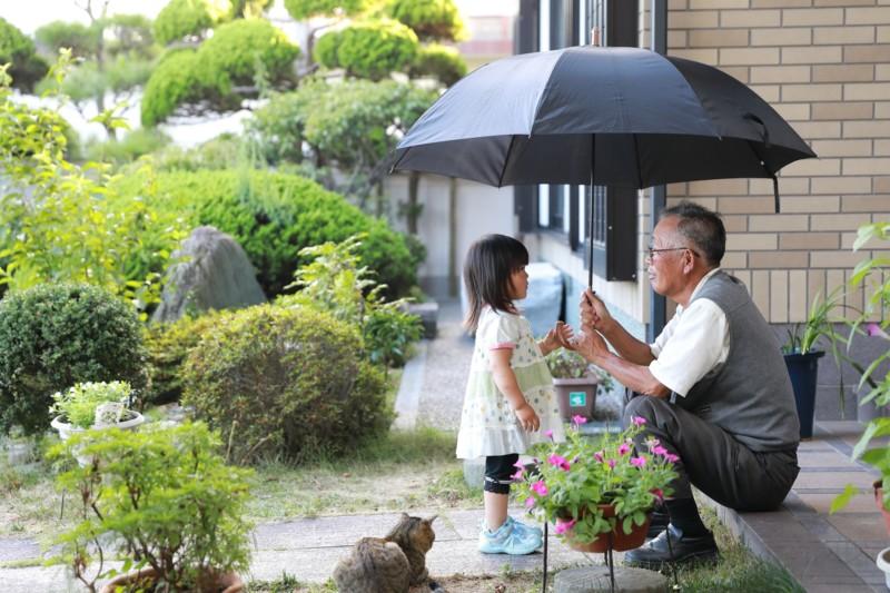 傘を差す老人と孫